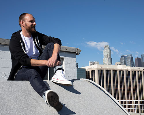 Man sitting on city rooftop